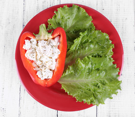 Stuffed pepper and lettuce on plate on wooden background