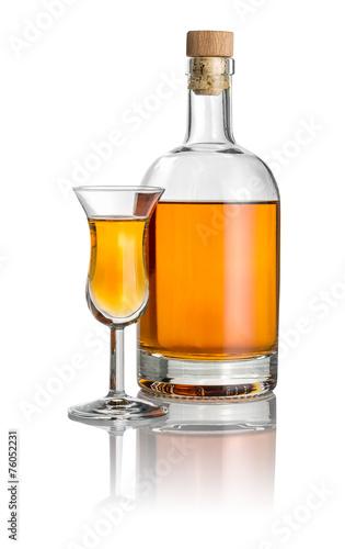 Fotobehang Alcohol Flasche und hohes Kelchglas mit bernsteinfarbener Flüssigkeit