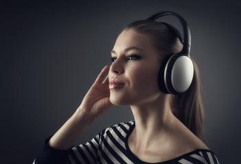 DJ girl in earphones listening disco beats over dark background