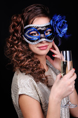 Beautiful girl with masquerade mask and glass of champagne
