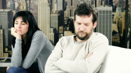 sad couple at home not speaking after fight