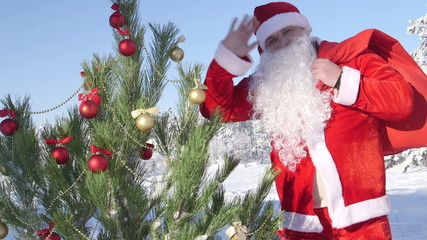Santa Claus waving his hand near decorated Christmas tree