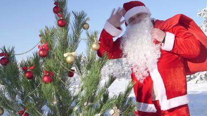 Santa Claus waving his hand near decorated Christmas tree