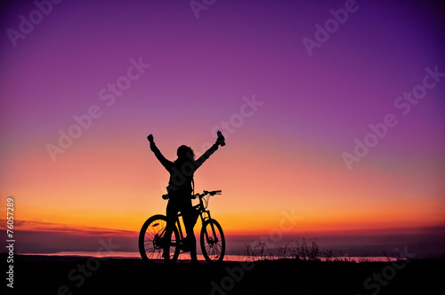 Girl with a bicycle watching the sunset - 76057289