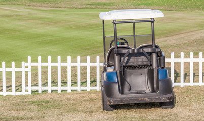 Golf cart parks near the white wooden fence around the golf cour