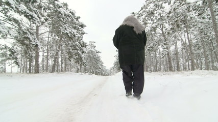 senior woman walking along the road through the winter