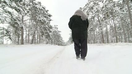senior woman walking along the road through the winter