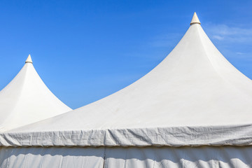 Top of white canvas tent with clear blue sky background