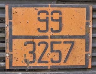 Orange plate with hazard identification number on bitumen tank