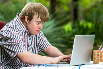 Concentrated handicapped boy typing on laptop.