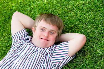 Handicapped boy relaxing on green grass.