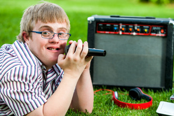 Handicapped boy singing with microphone and amplifier.
