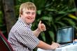 Leinwanddruck Bild - Handicapped student working on laptop.