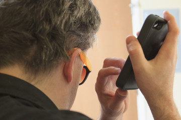 Blind man using assistive listening in his cell phone