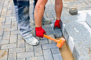 Construction worker putting concrete paving stones.