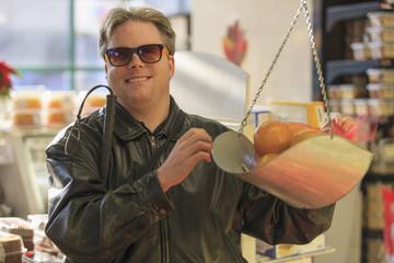 Blind man weighing fruit at the supermarket