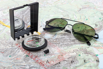 Compass and pilot sunglasses on a hiking map