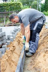 Construction worker place border stones.