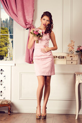 Young beautiful woman in pink dress. Fashion model shooting.