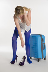 Woman in blue tights putting on high heel shoes