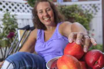 Woman with Spina Bifida enjoying fruit in the summer