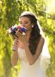 portrait of elegant brunette bride smelling wedding bouquet