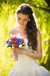 happy brunette bride looking at wedding bouquet at park