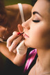 professional makeup artist painting woman lips with brush
