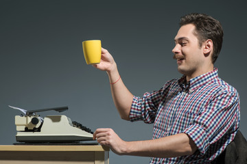 Author drinking coffee at typewriter