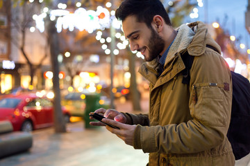 Outdoor portrait of young man using his mobile phone at night.