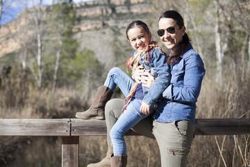 Madre e hija apoyadas en puente de madera