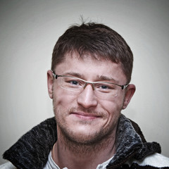 Portrait of a smiling young man with glasses, studio shot