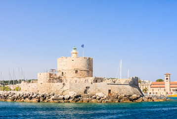Old fortress with lighthouse in the port of Mandraki. Rhodes Isl