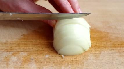 Man slicing onion on wooden board