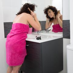 Femme souriante face à son miroir