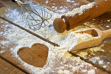 flour, rolling pin and heart with wood background