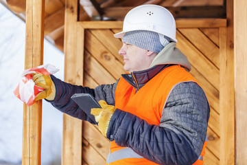 Carpenter with tablet PC near wooden building