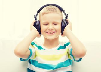smiling little boy with headphones at home