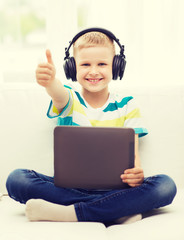 little boy with tablet pc and headphones at home