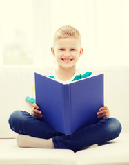 smiling little boy reading book on couch