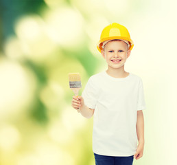 smiling little boy in helmet with paint brush