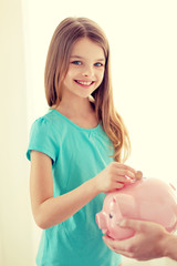 smiling little girl putting coin into piggy bank