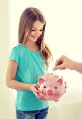smiling little girl holding piggy bank