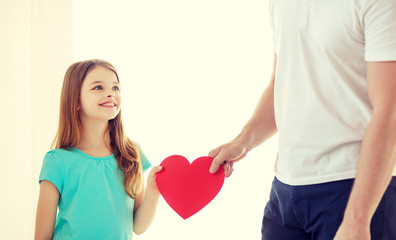 smiling little girl and father holding red heart