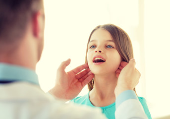 male doctor checks little girl lymph nodes