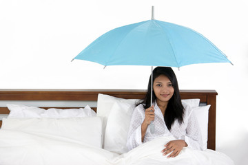 woman holding umbrella and sitting in bed