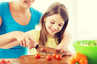 smiling little girl with mother chopping tomatoes