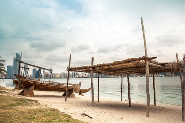 sea beach with old wooden boath and luxury skyscarper