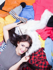 Young happy woman lying down on a pile of clothes
