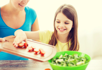 little girl with mother adding tomatoes to salad